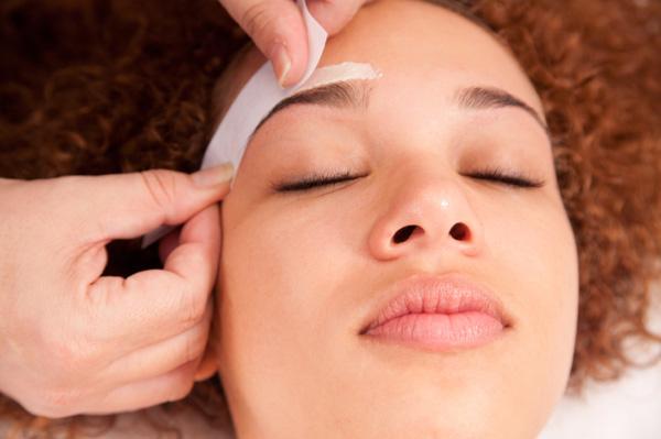 Woman having eyebrows waxed