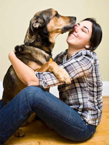 Woman getting licked by dog