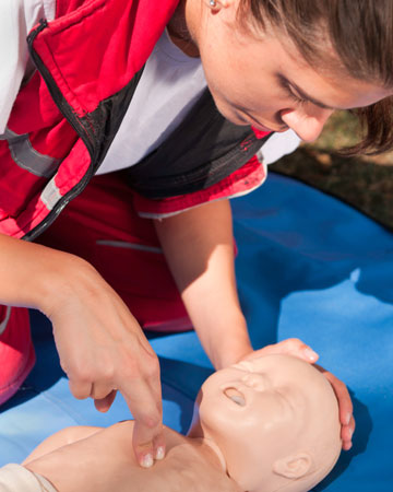 Mother learning to give infant CPR