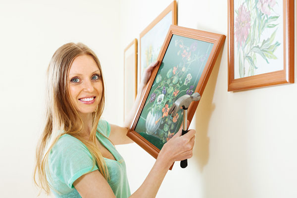 Woman hanging paintings | Sheknows.com