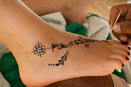 Woman getting henna tattoo on feet