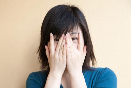 Woman hiding behind hands