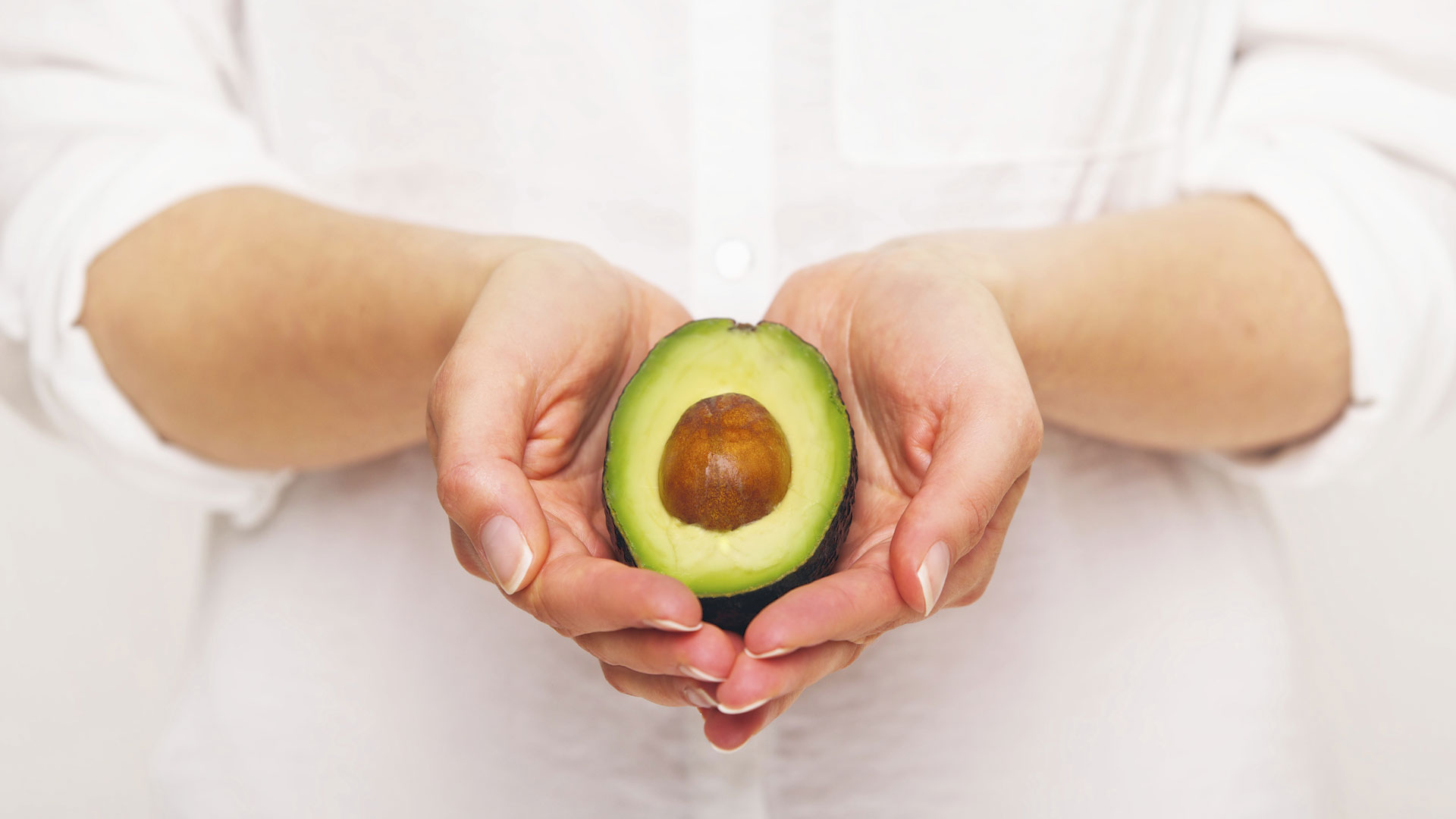Woman holding a sliced avacado