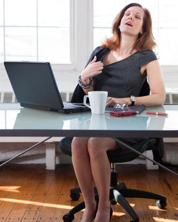Woman having hot flash in office