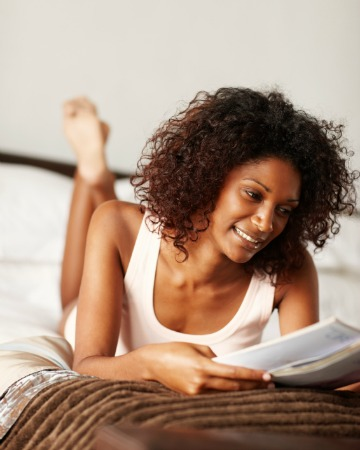 Woman relaxing and reading in bed
