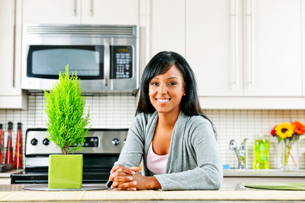 Woman in kitchen with houseplant