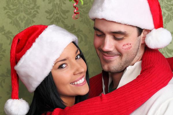 Woman kissing man under mistletoe
