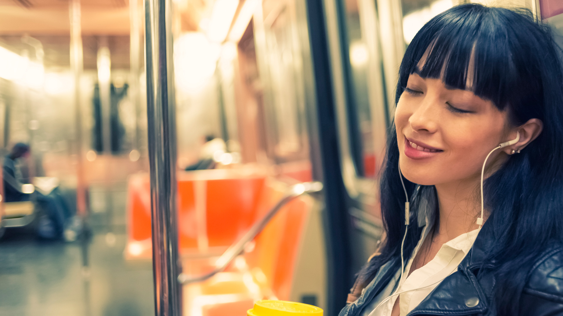Woman listening to audiobook on subway