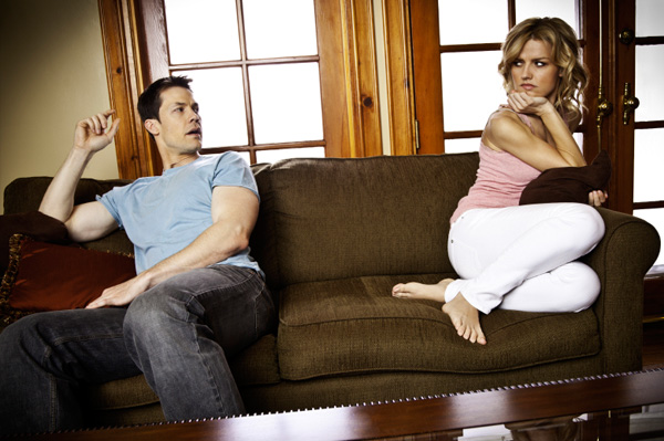 Woman looking at her husband on the couch