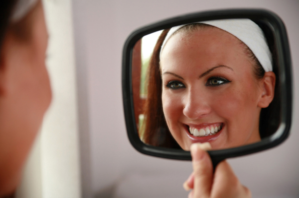 woman looking at teeth in a mirror