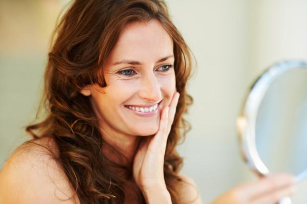 Happy woman looking in mirror