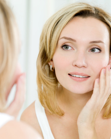 Woman looking in mirror and touching face