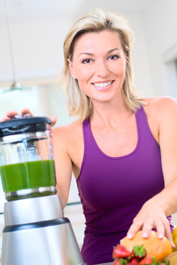 woman making smoothie after workout