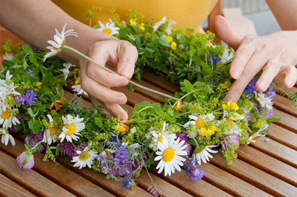 woman creating wreath with flowers
