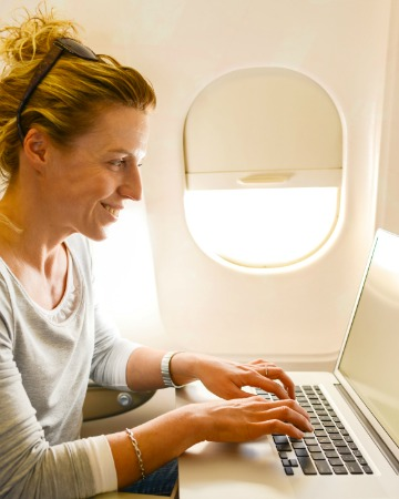 Woman on laptop on a plane