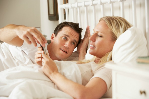 Woman on smartphone in bed
