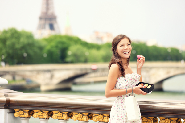 Woman eating macaroon in Paris