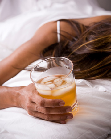 Woman passed out on bed with drink in hand