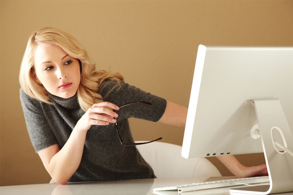 Woman peering around computer