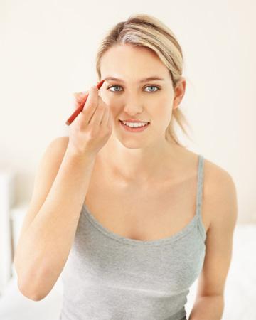 Woman penciling in eyebrows