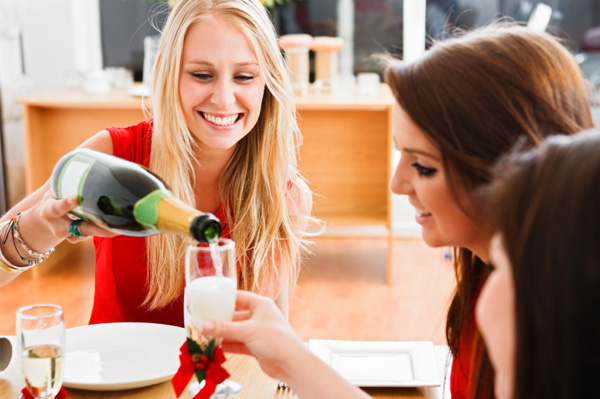 Woman pouting champagne at Christmas party