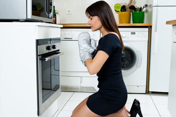 Woman praying in front of stove