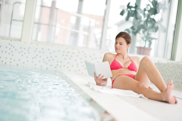 Woman reading book by pool