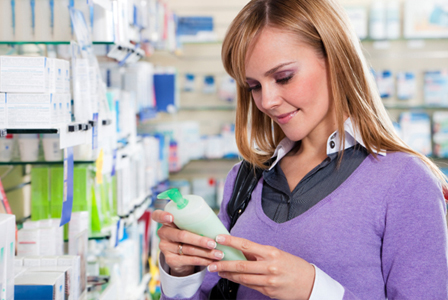 Woman reading lotion bottle