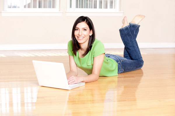 Woman using laptop on hardwood floor