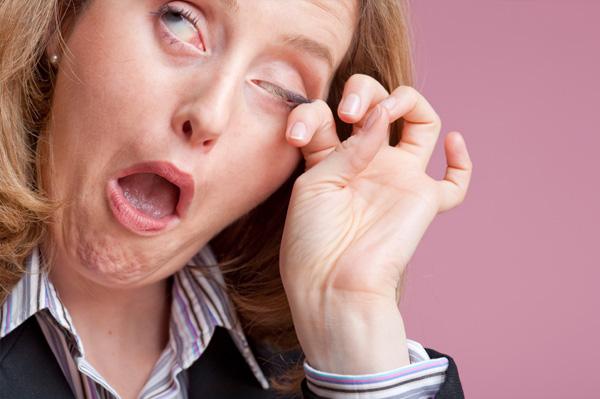 Woman rubbing eyes