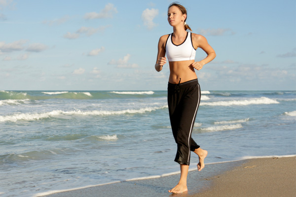 Woman running down beach