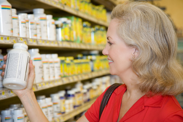 Woman selecting probiotics from shelf