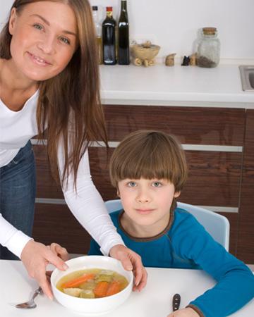 Woman serving son soup