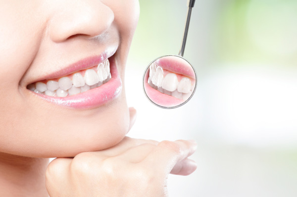 Woman smiling in dentist mirror
