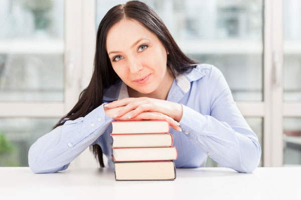 Woman smiling over stack of books