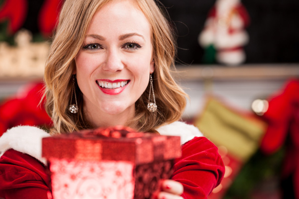 Young woman smiling while handing the camera a beautifully wrapped Christmas gift