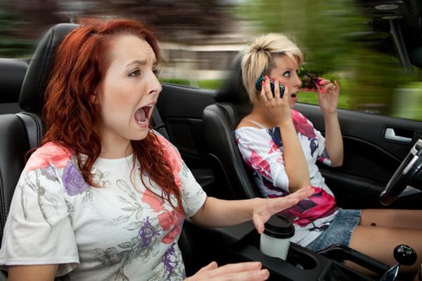 Woman driving and applying makeup