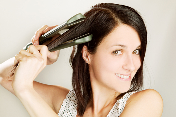 Woman straightening hair with flat iron