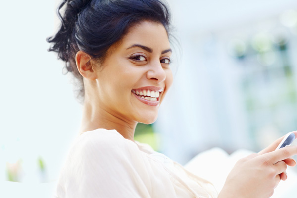 smiling woman typing on smartphone