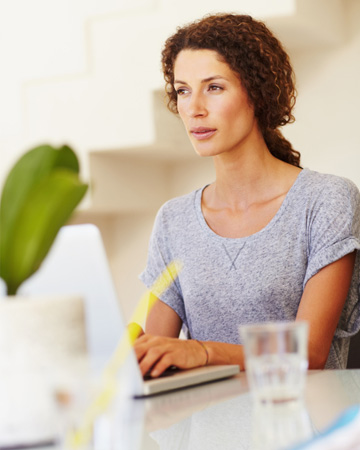 Woman thinking at computer