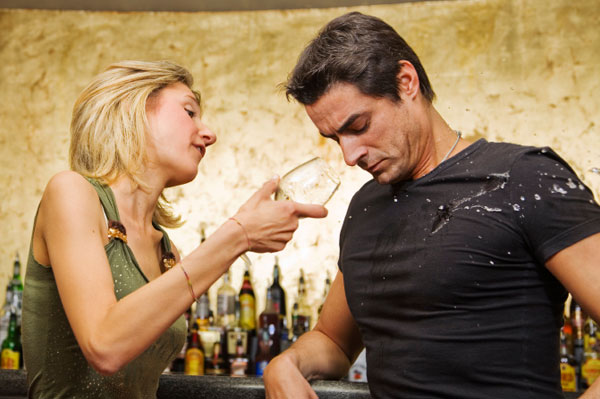 Woman throwing drink at man