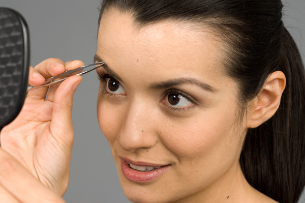 Woman tweezing her eyebrows