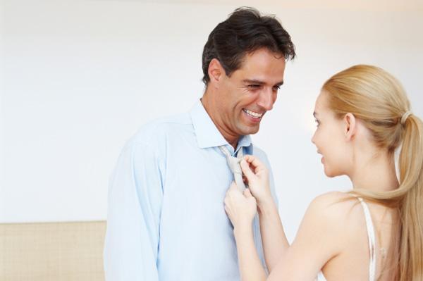 Woman tying man's necktie