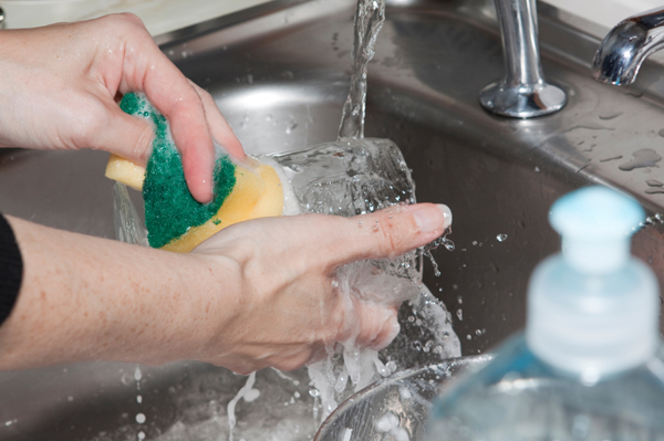 woman pre-washing dishes in sink