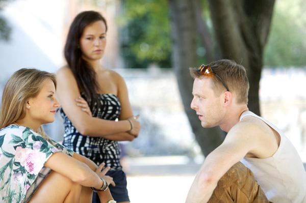 Woman watching boyfriend talking to female friend