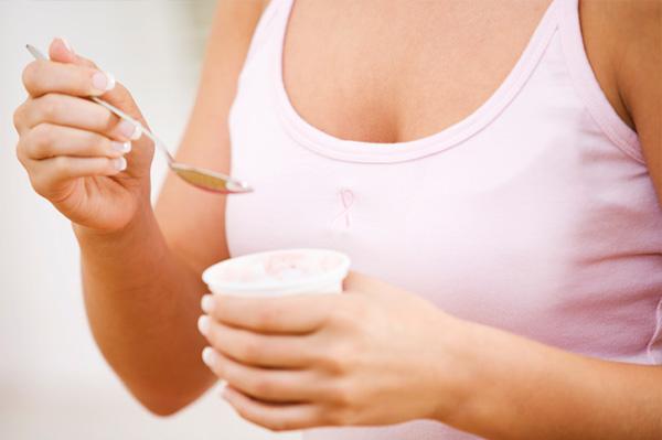 Woman wearing breast cancer ribbon eating yogurt