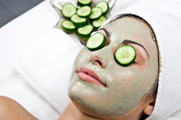 Woman wearing facial mask and cucumbers