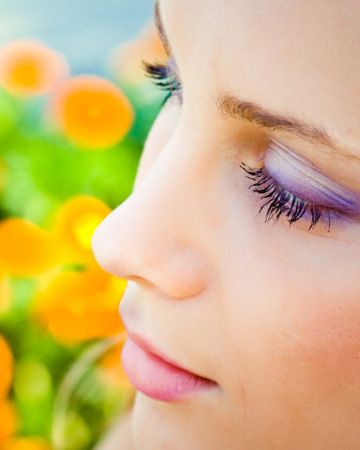 Woman wearing pastel makeup against blurred flower background