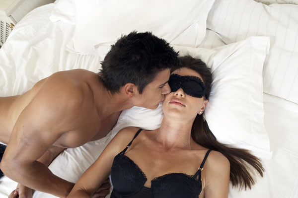 Couple in bed with woman blindfolded.