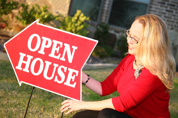 Woman with open house sign